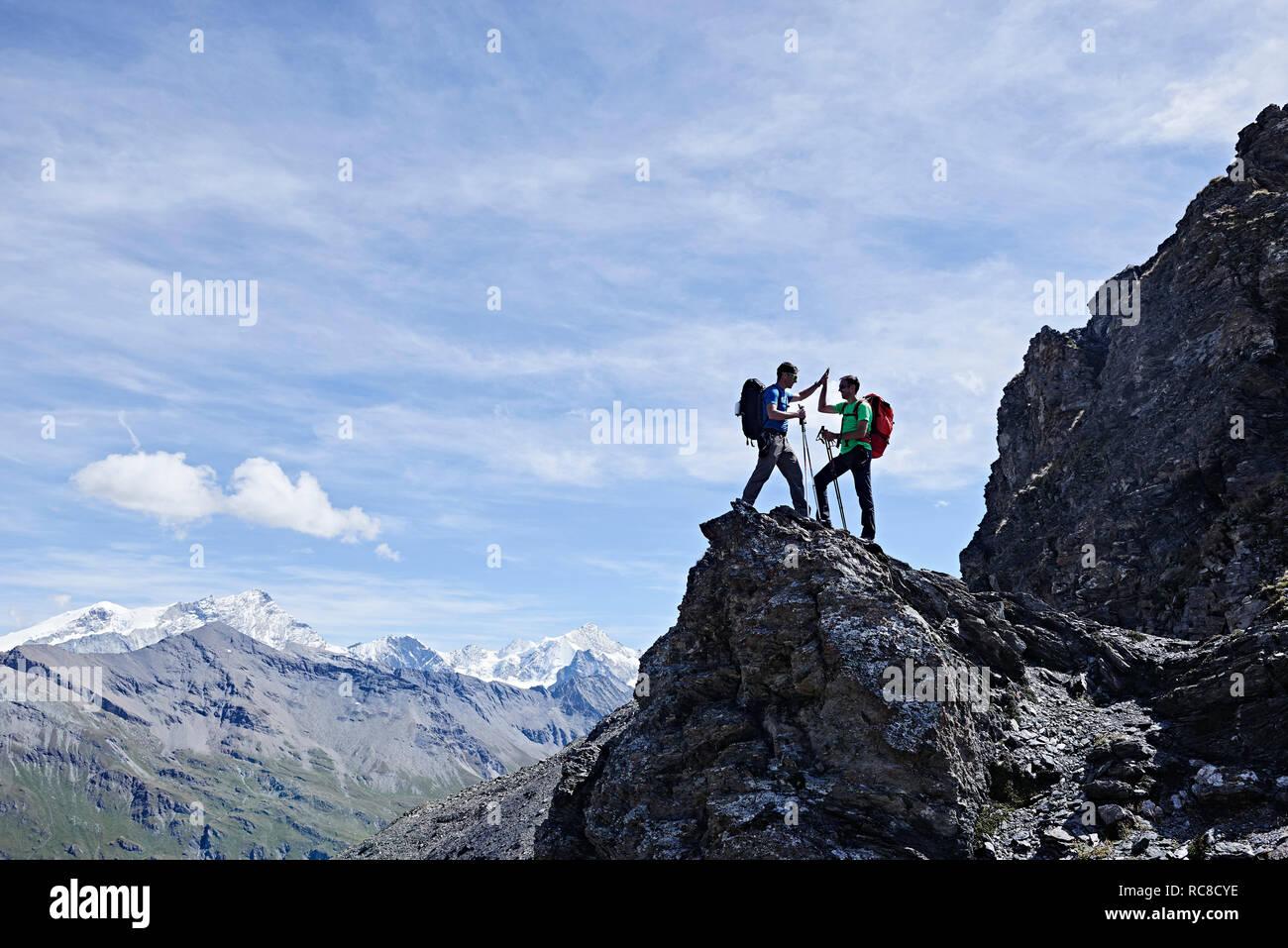 Gli escursionisti di alta fiving sul picco di roccia, Mont Cervin, Cervino, Vallese, Svizzera Foto Stock