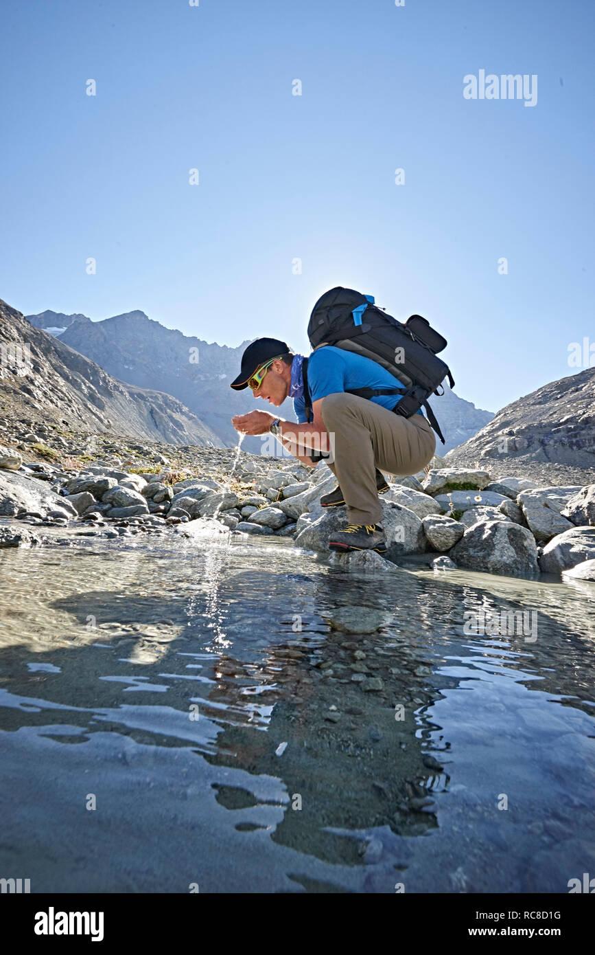 Escursionista bere da piscina, Mont Cervin, Cervino, Vallese, Svizzera Foto Stock