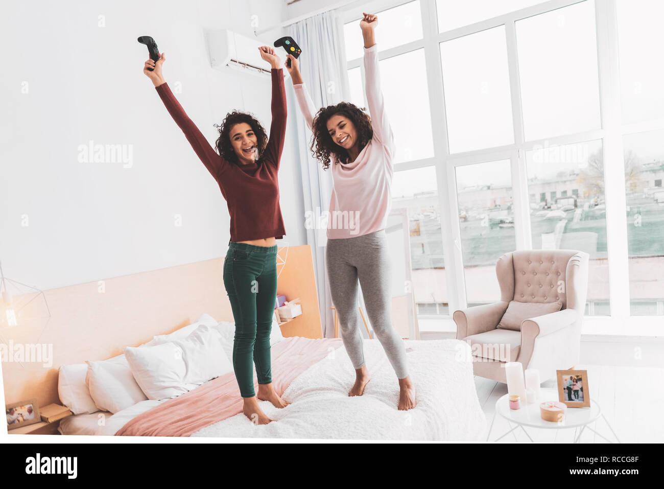 Curly felice ragazze salta allegramente sul letto matrimoniale foto