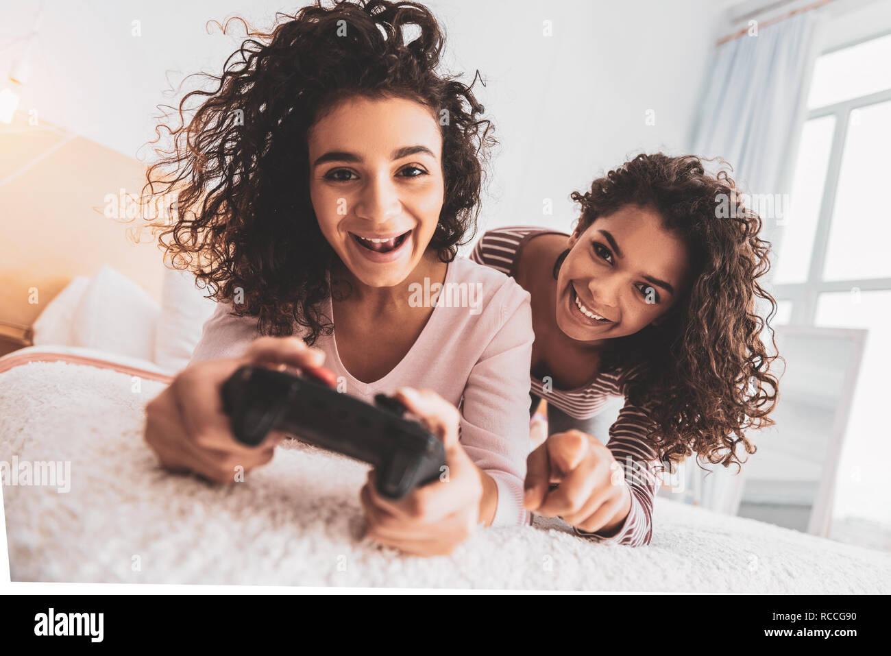 Gli amici di ridere mentre spendere il tempo libero con la play station Immagini Stock