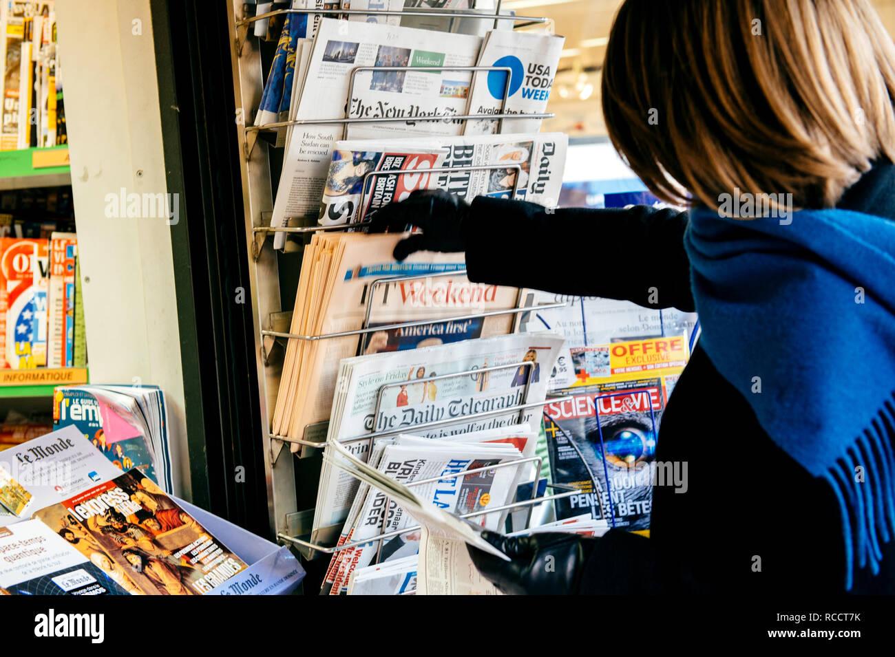 Parigi, Francia - 21 GEN 2017: Donna acquisto in media press kiosk il Financial Times Weekend edition con Donald Trump il presidente statunitense ant l'America primo slogan Immagini Stock