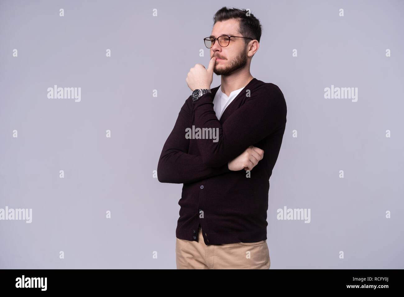 Giovane uomo bello pensare su sfondo grigio. Immagini Stock