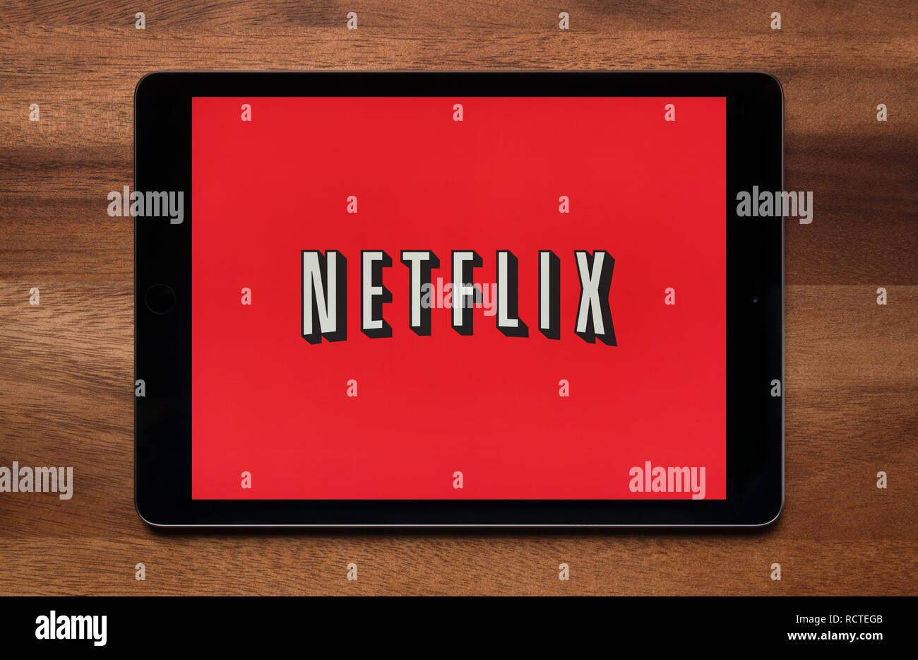 Il sito web di Netflix è visto su un tablet iPad, il quale è appoggiato su un tavolo di legno (solo uso editoriale). Immagini Stock