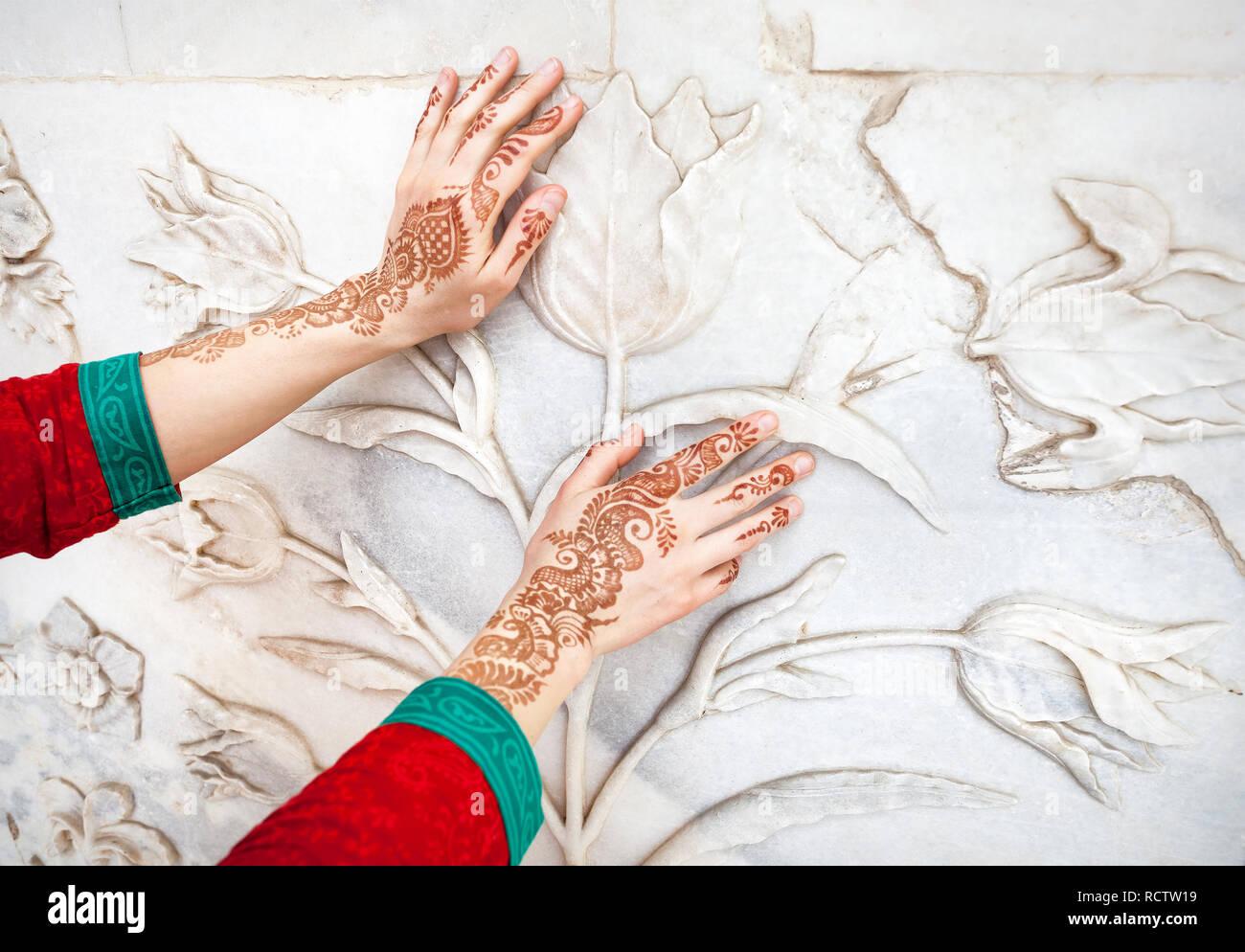 ed5a443d45ca Woman in Red costume indiano toccando il marmo bianco parete con motivo  floreale dalle mani di