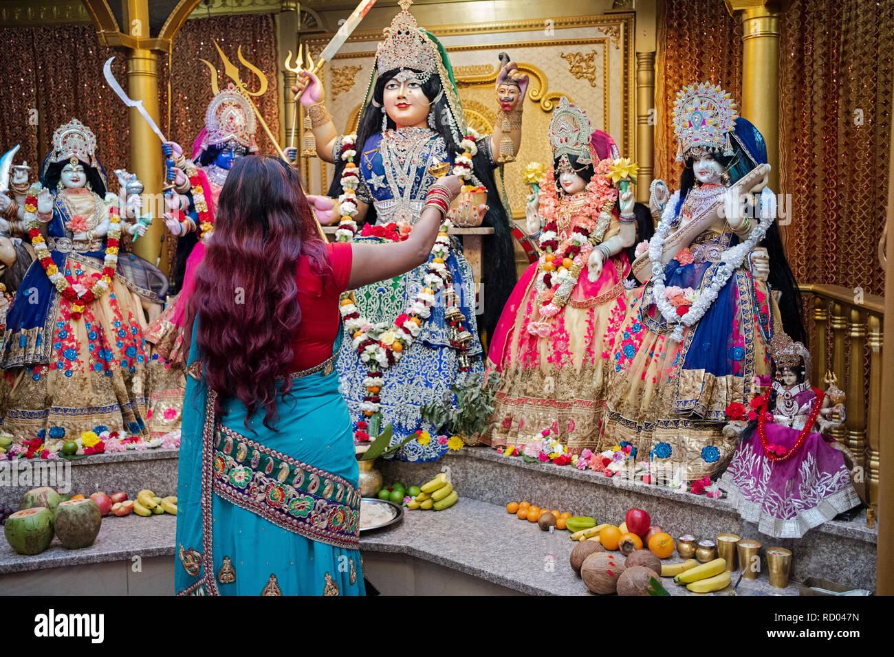 Le arti rituale. Una pia donna Indù prega e onde fuoco davanti di statue di divinità in un tempio nel Queens, a New York City. Immagini Stock