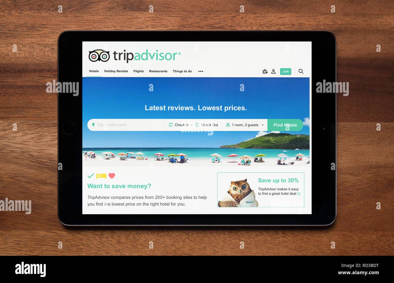 Il sito di Trip Advisor è visto su un tablet iPad, il quale è appoggiato su un tavolo di legno (solo uso editoriale). Immagini Stock