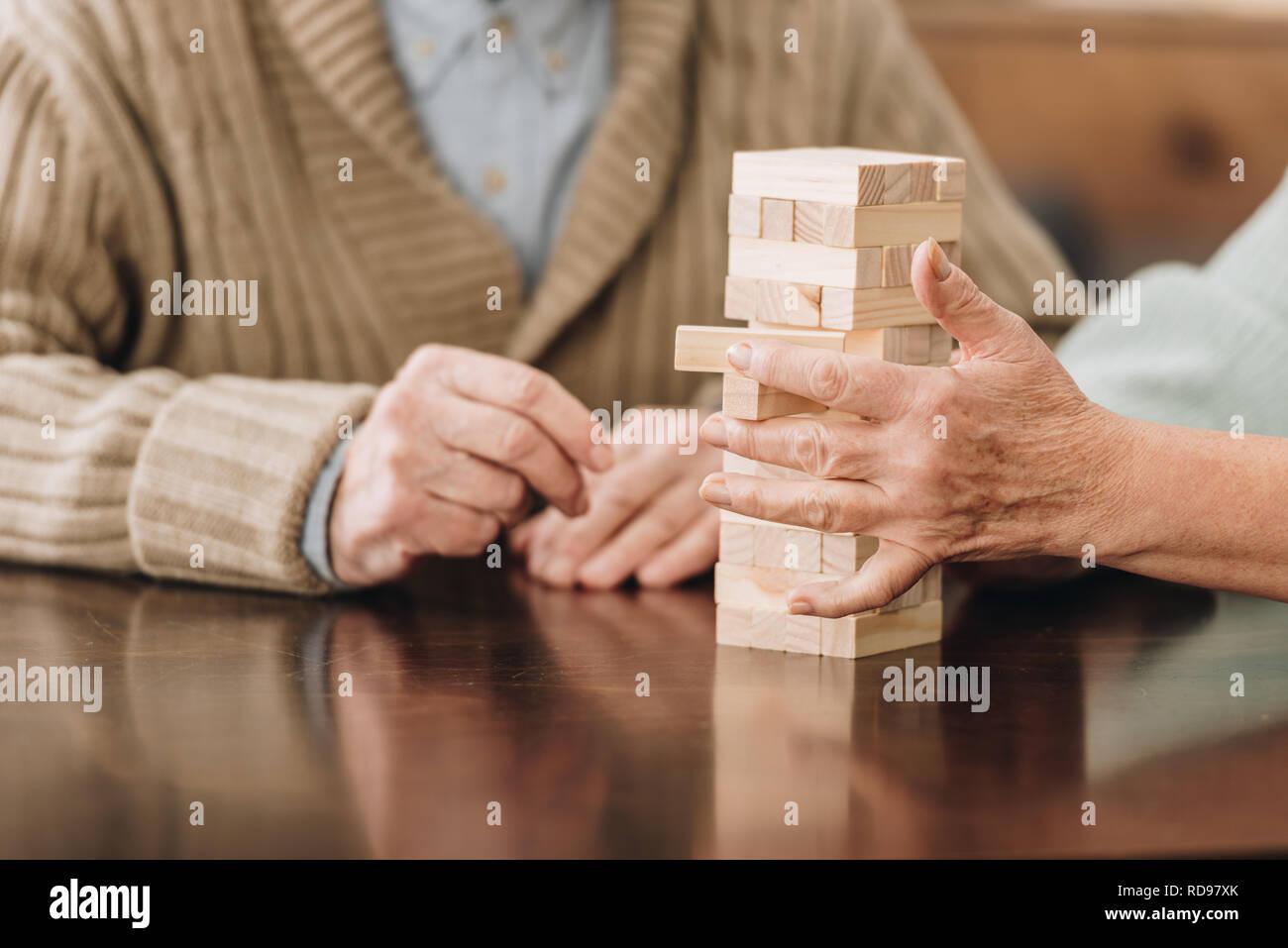 Vista ritagliata della coppia senior giocando jenga a casa Foto Stock