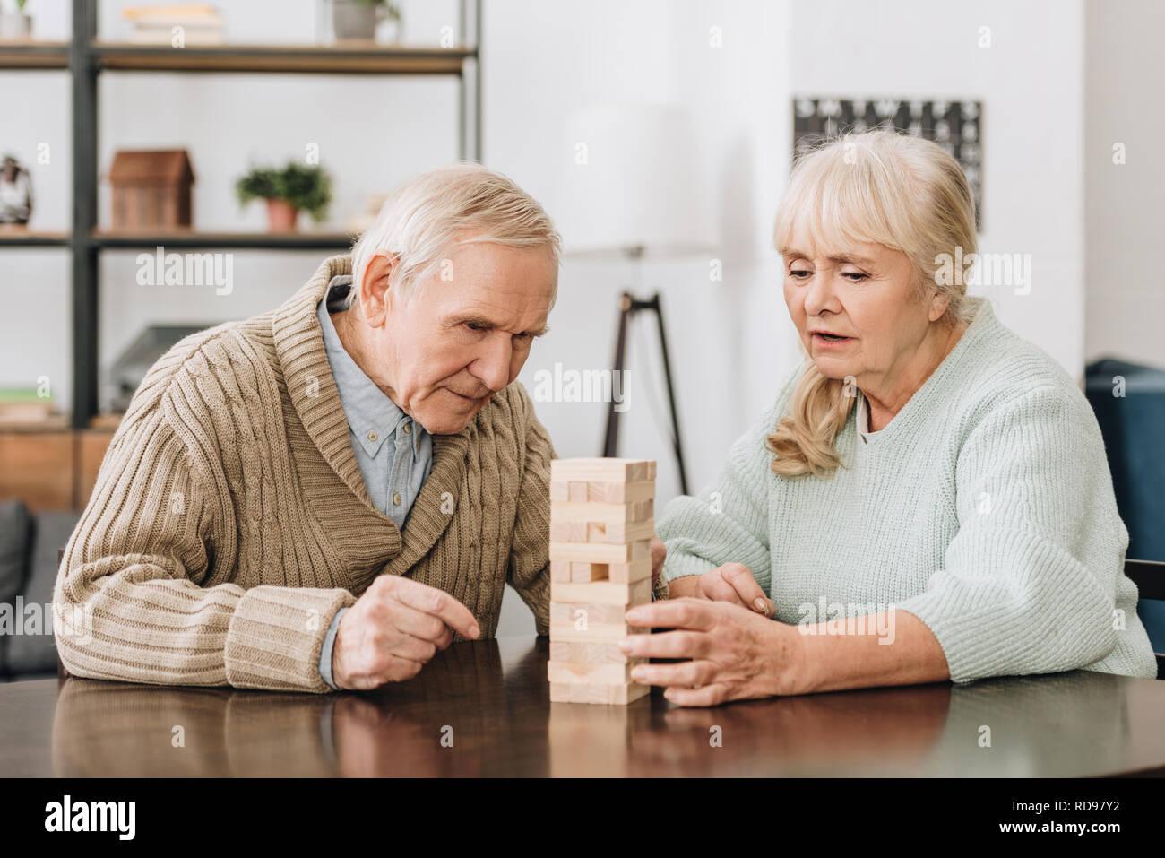 Coppia senior giocando con dei blocchi di legno a casa Foto Stock