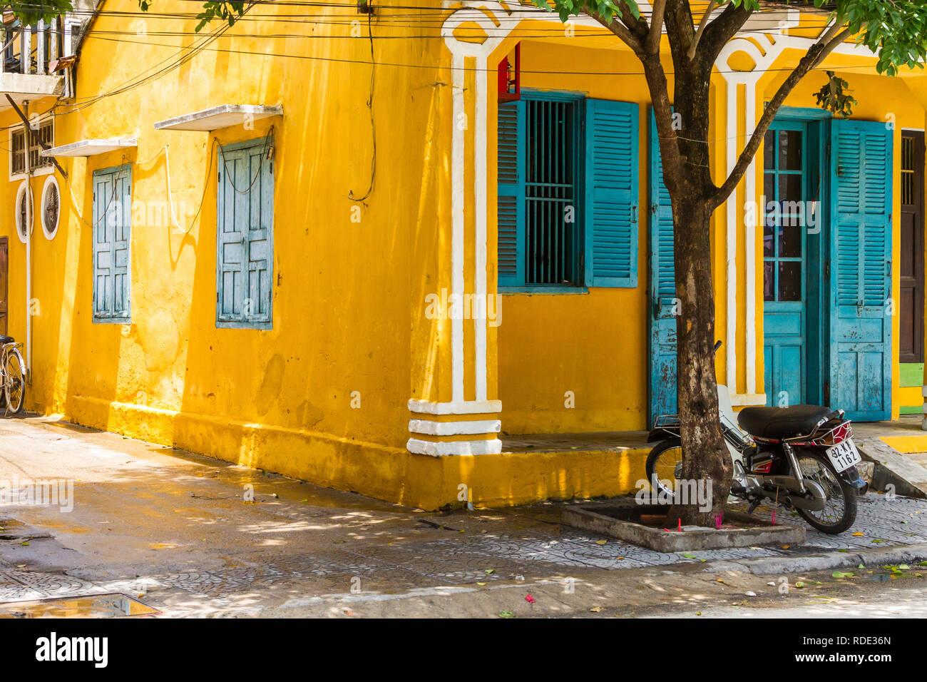 Vista anteriore e laterale di colore giallo brillante edificio con persiane blu e porte in Hoi An, Vietnam con moto accanto a tree Immagini Stock
