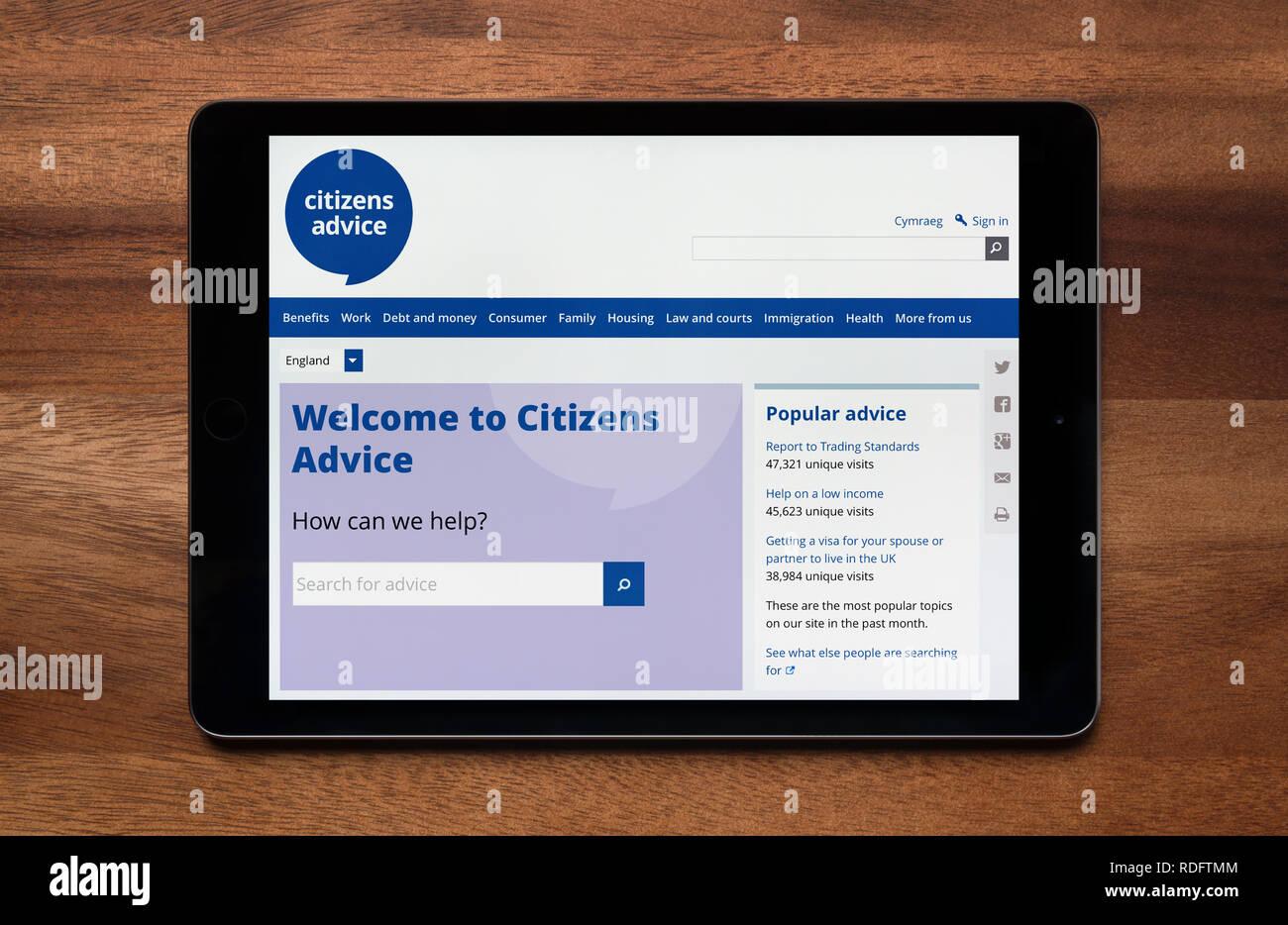 Il sito di consulenza per i cittadini è visto su un tablet iPad, il quale è appoggiato su un tavolo di legno (solo uso editoriale). Immagini Stock