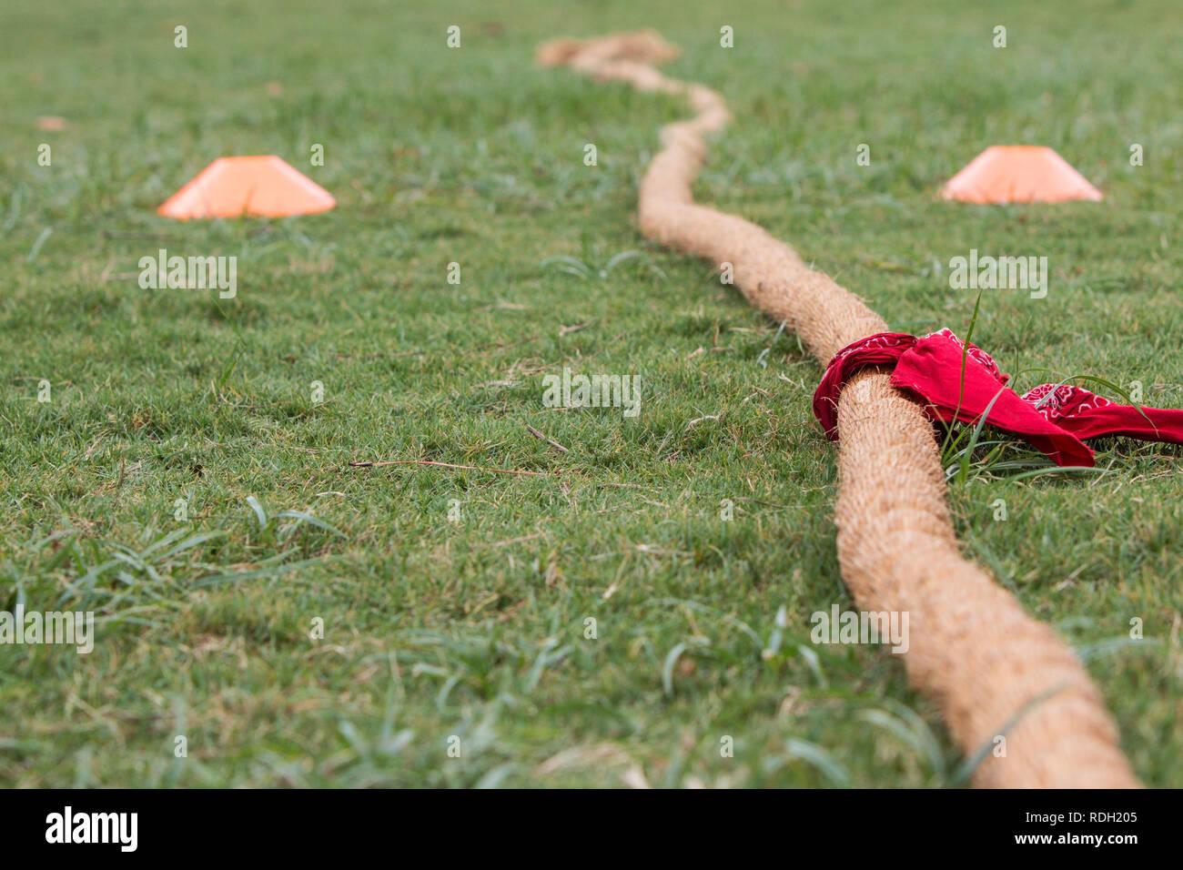 Corda spessa con red bandana attaccato giace sull'erba prima dell inizio del rimorchiatore di concorso di guerra Immagini Stock
