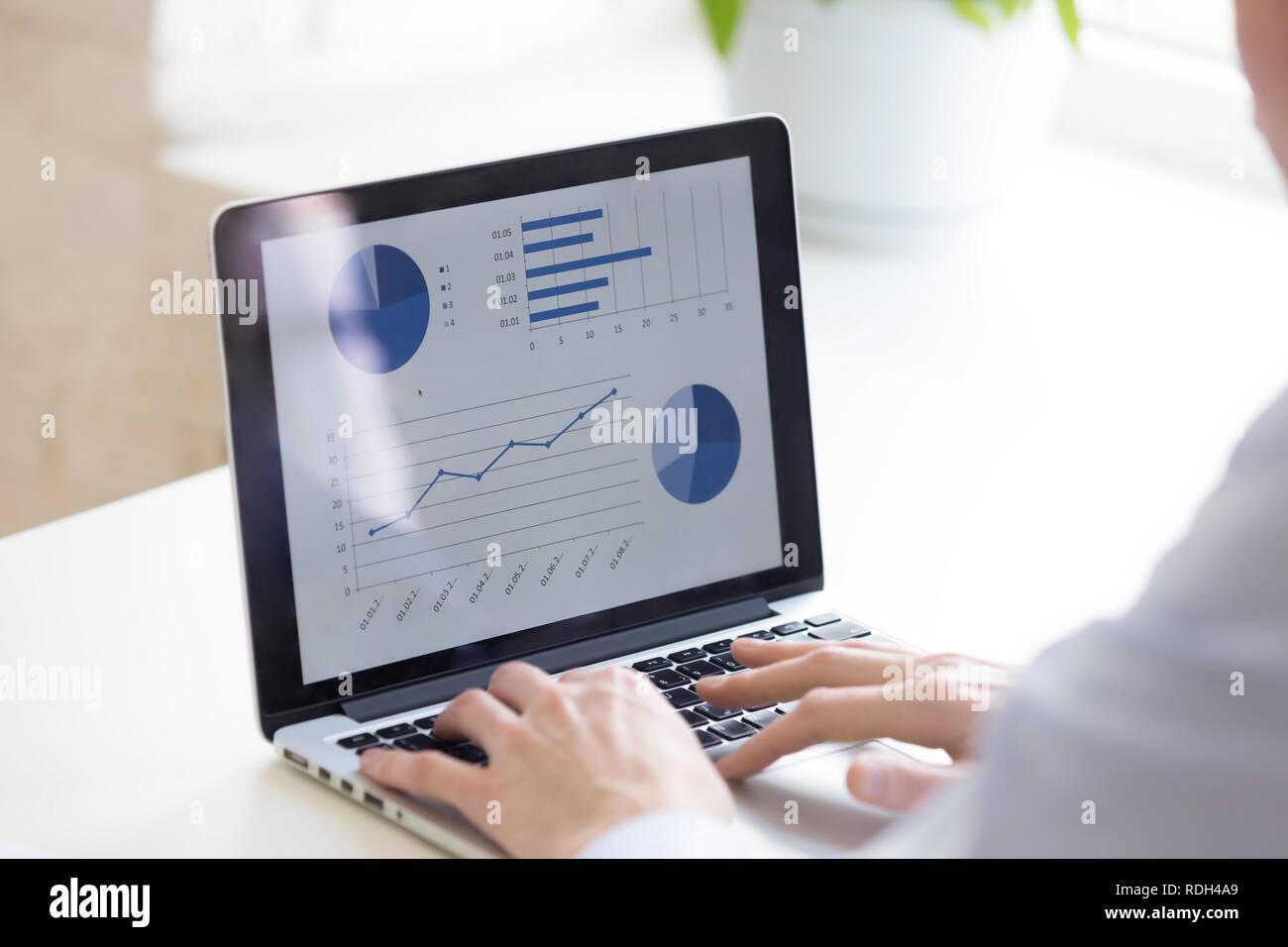 Chiudere l uomo d affari con computer portatile, analizzare le statistiche delle imprese Immagini Stock