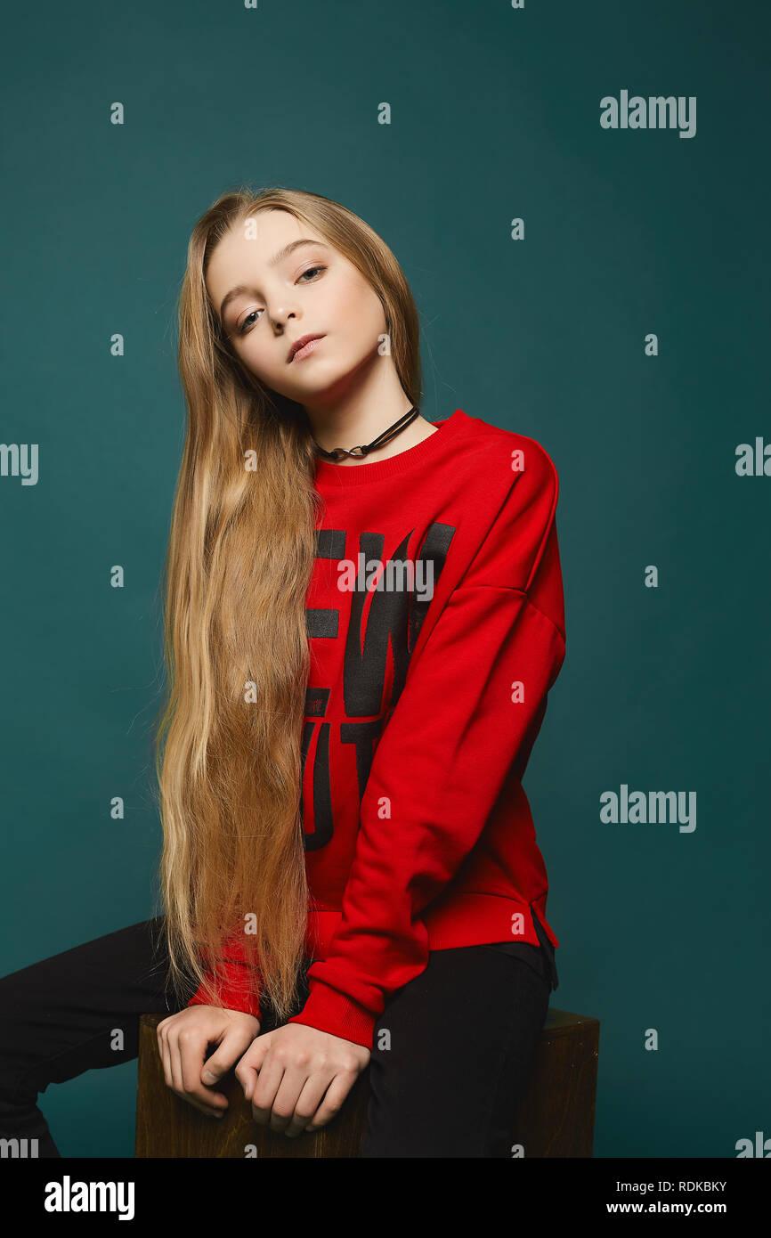 Elegante teen, giovane e bella ragazza modello con lunghi capelli biondi in jeans nero e nel quartiere alla moda di felpa rossa in posa presso lo studio Immagini Stock