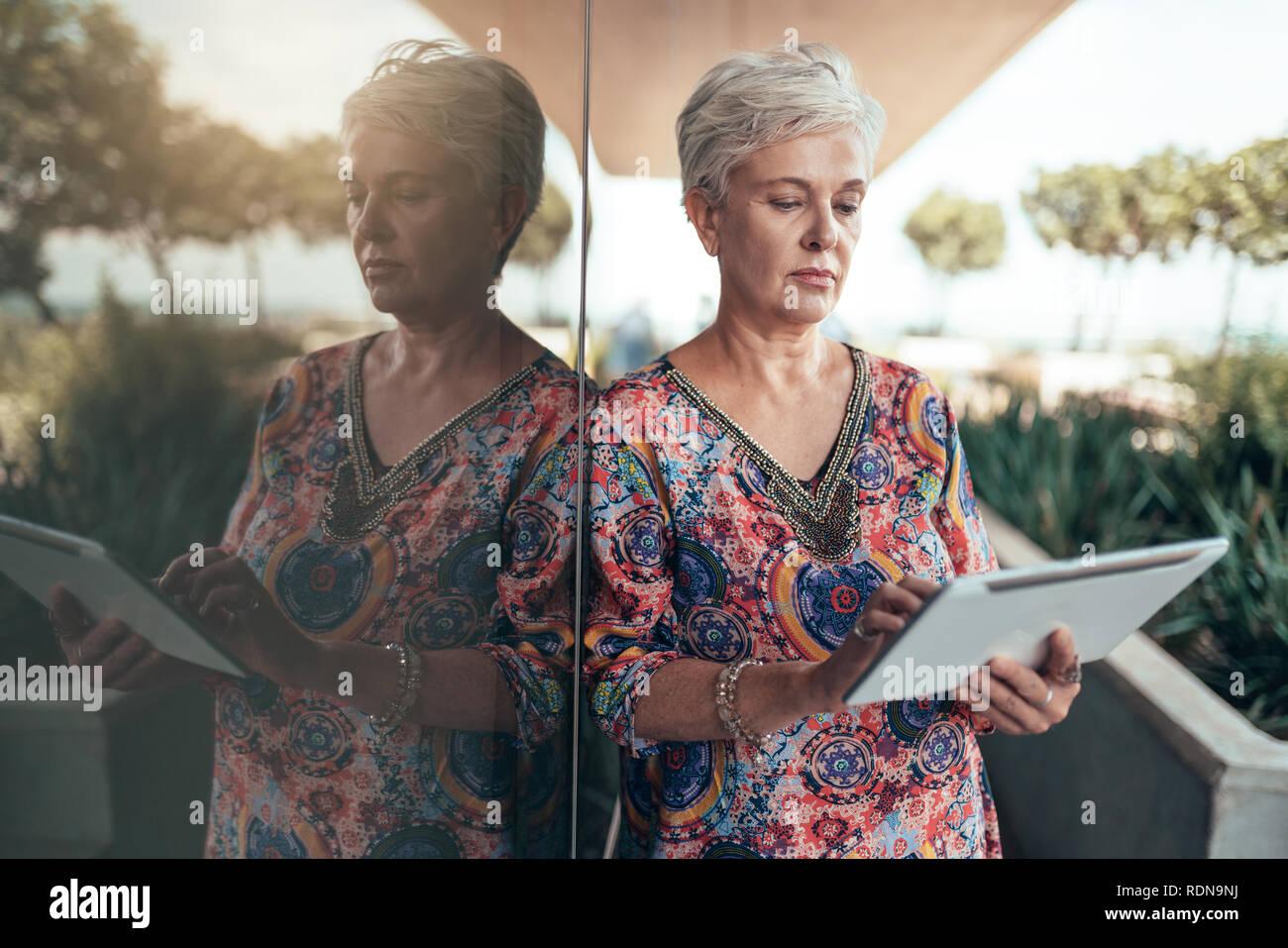 Ritratto di un bellissimo pelo grigio donna di mezza età lavorando su tavoletta digitale Foto Stock