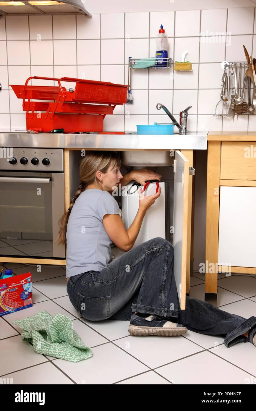 Giovane donna la riparazione di un guasto rubinetto di acqua in una cucina Immagini Stock