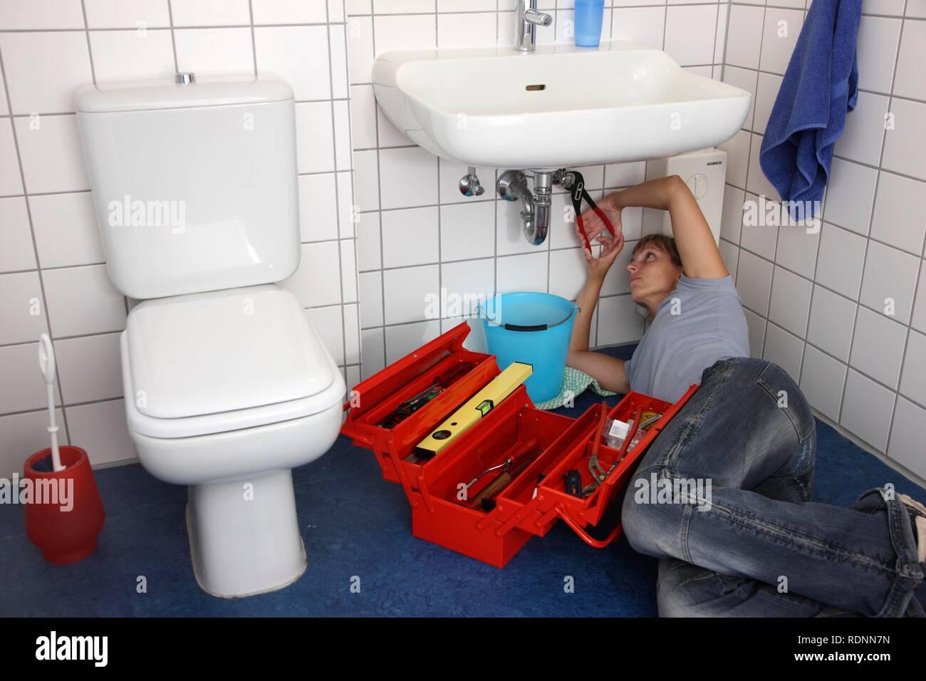 Giovane donna la riparazione di un guasto rubinetto di acqua in un bagno Immagini Stock