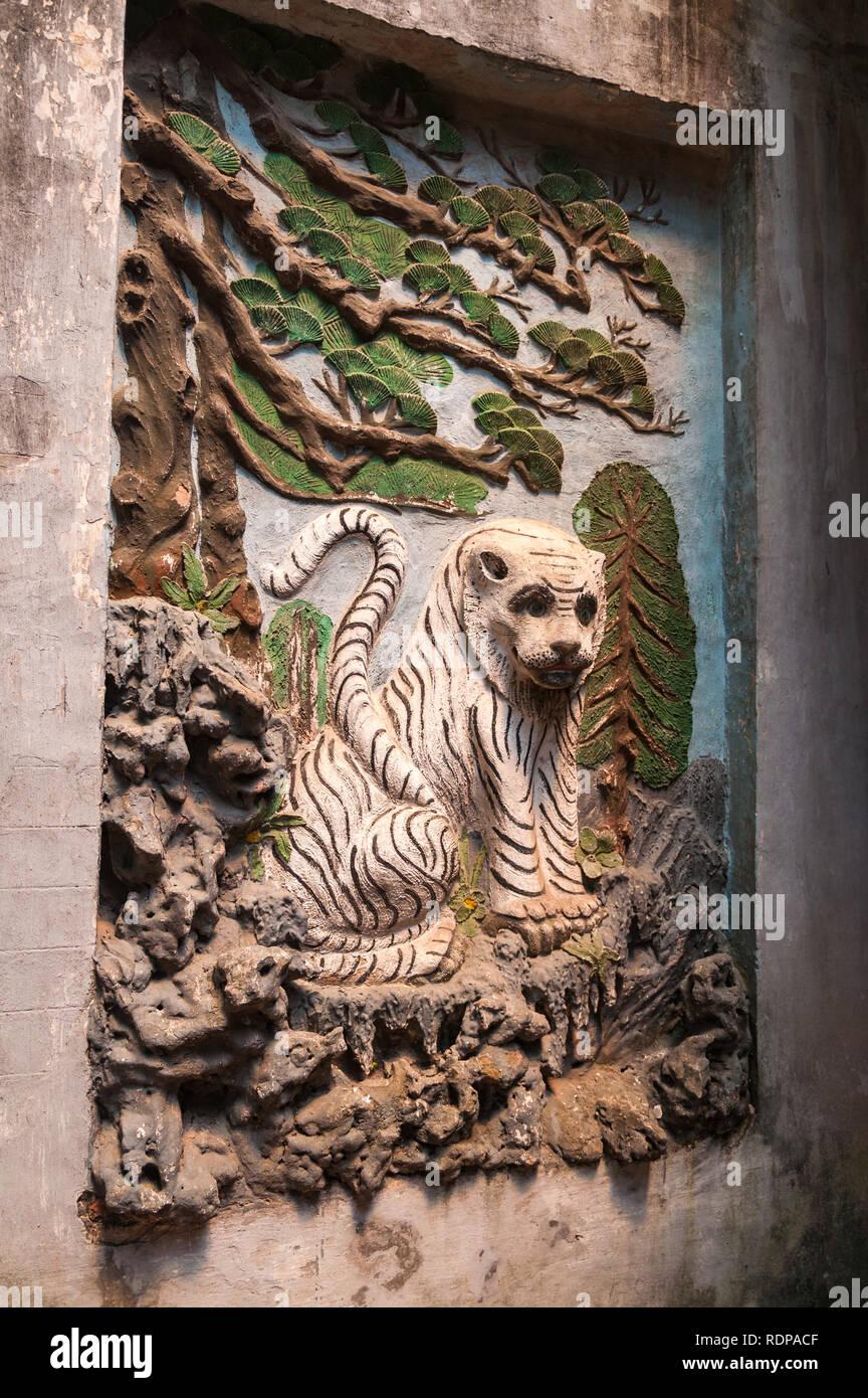 Pietra di sfiato artwork simbologia animale di una tigre sotto un albero sulla parete del taoista Thánh Quán tempio ( Đền Quán Thánh ), Hanoi, Vietnam Immagini Stock