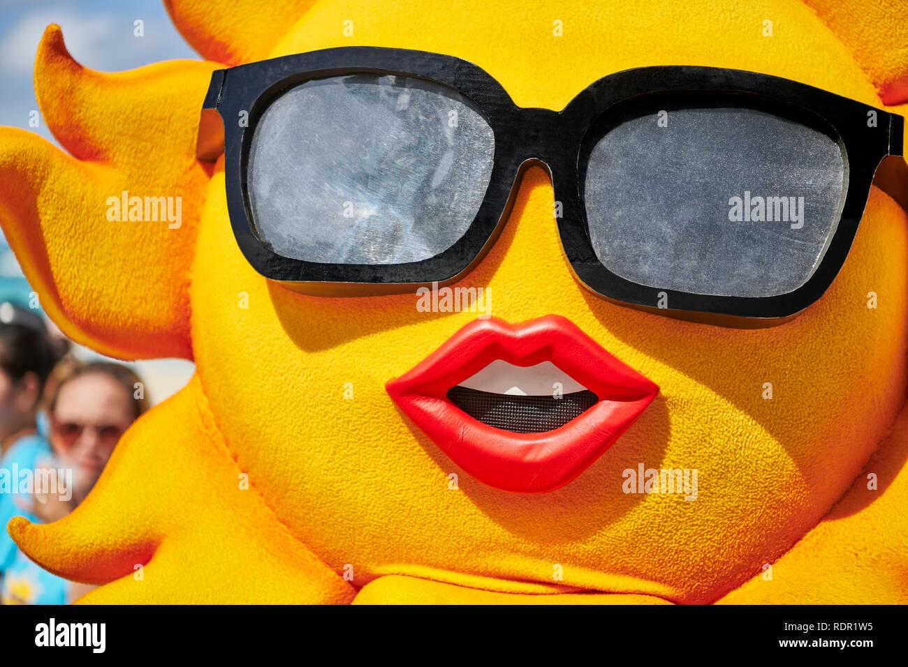 Partecipante al festival Ati-Atihan parade sulla bianca spiaggia di Boracay Island che indossa un costume di Sun con un gigante di occhiali da sole Immagini Stock