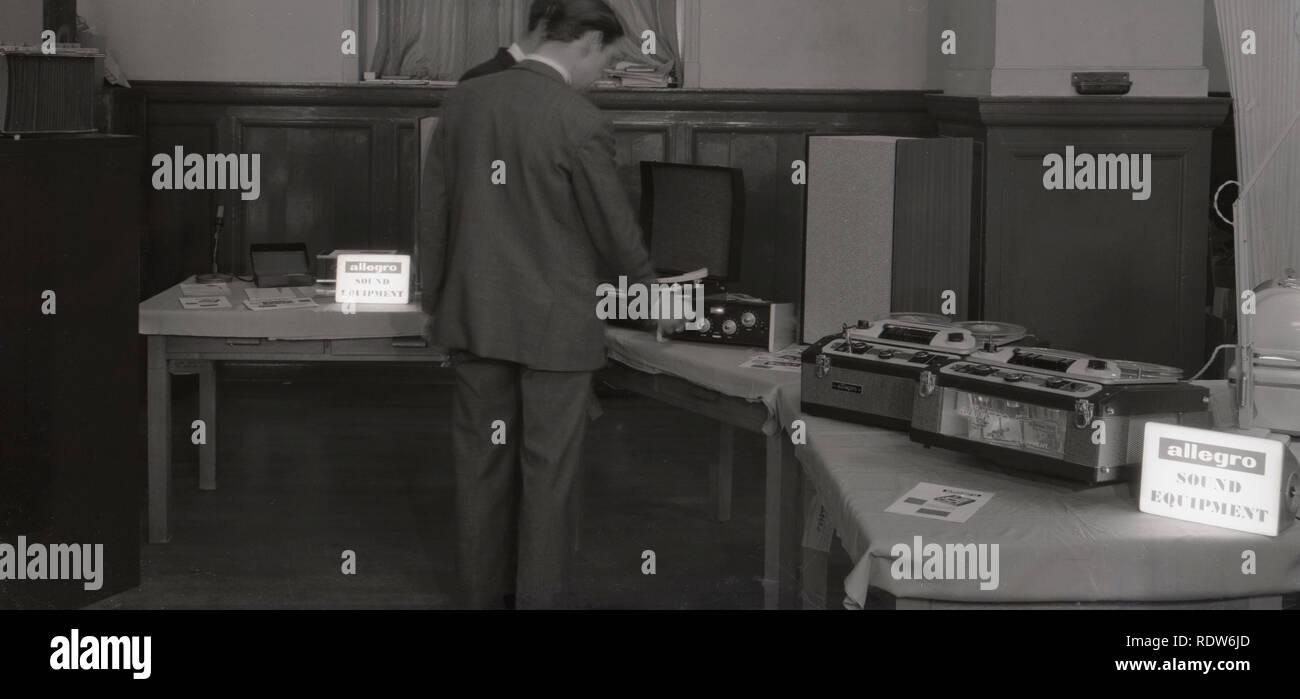 Degli anni Cinquanta, uomo guardando una piscina espositivo delle ultime allegro suono, comprese le attrezzature da nastro a nastro Macchine di registrazione e il vinile giradischi, England, Regno Unito Immagini Stock
