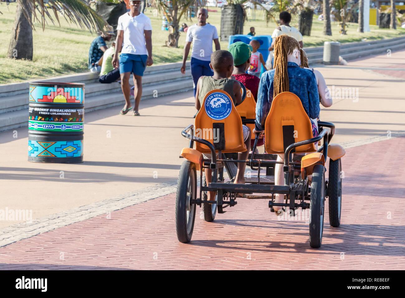 Durban, Sud Africa - Gennaio 06th, 2019: Due ragazzi neri e due bianchi-caucasica ragazze la condivisione di un quadriciclo per un giro in spiaggia di Durban, Sud Immagini Stock