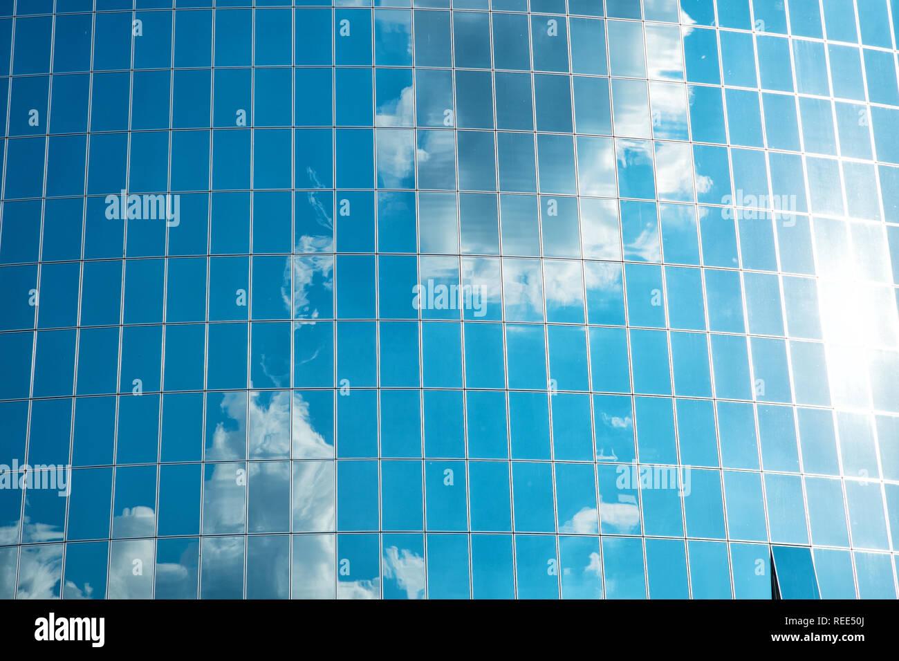 Nuvole riflettono sulla facciata in vetro e la parete dell'edificio. Nuvoloso cielo blu riflessione in Windows. Moderna architettura di vetro. Fondo di architettura. struttura e design. Futuro e dello sviluppo. Foto Stock
