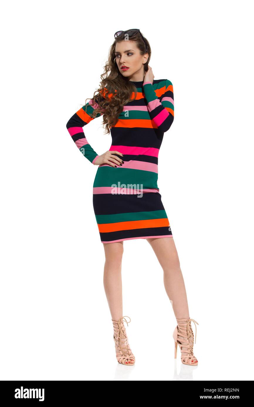 b84ba996a94c Moda sierosa nel modello a strisce colorate mini dress e tacchi alti è  tenendo la mano