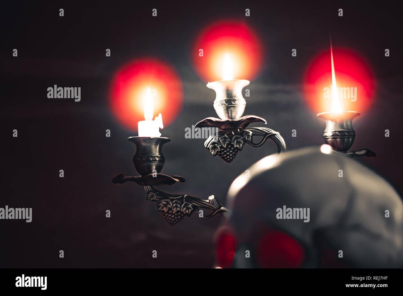 Illuminazione delle candele del cranio con candela e libri sulla