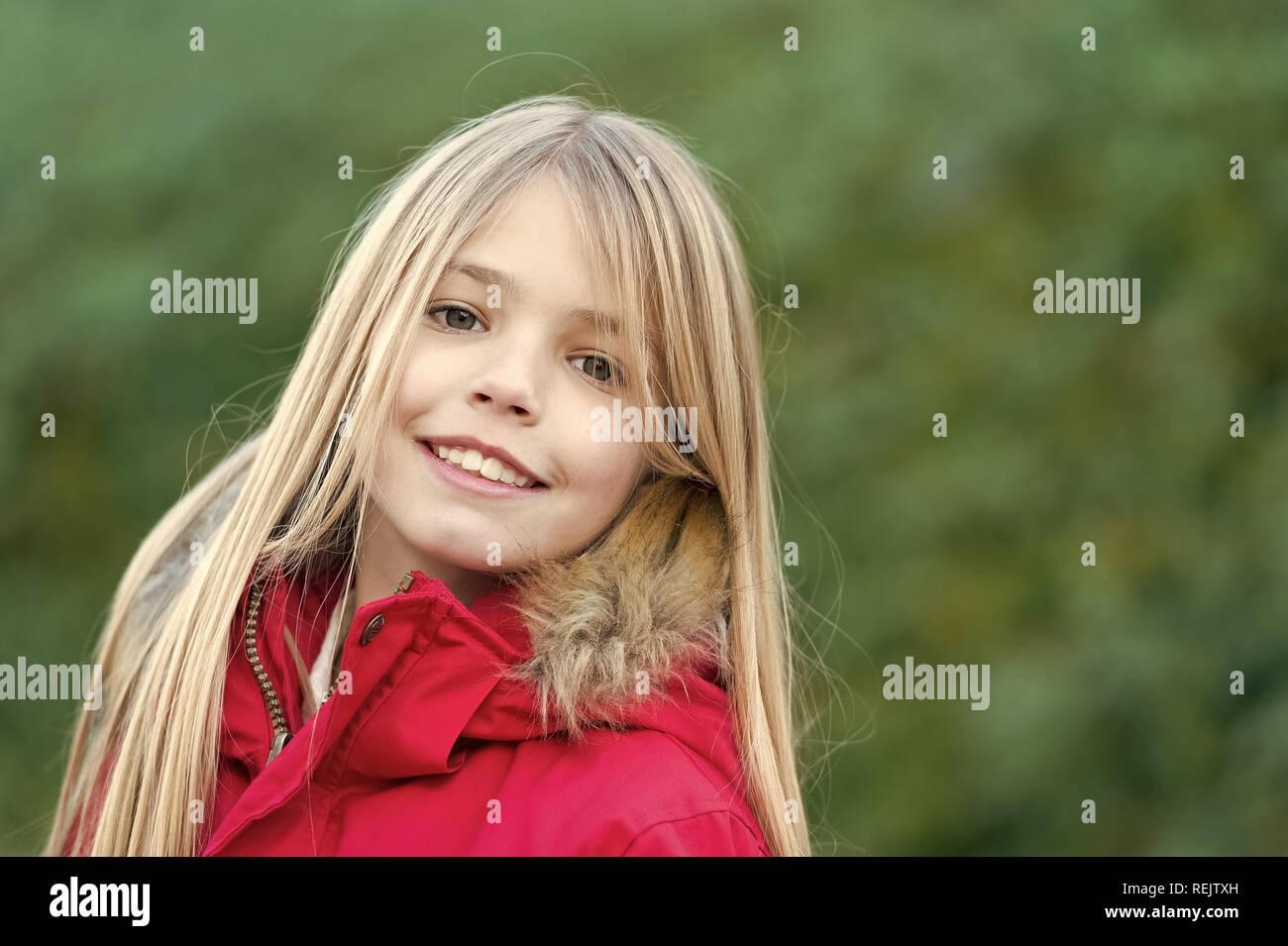 L'innocenza, la purezza e la gioventù. Ragazza bionda con capelli lunghi sorriso sull ambiente naturale. Infanzia felice concetto. Bellezza, natura, crescita. Bambino in rosso cappotto godere idilliaco giorno d'autunno. Immagini Stock