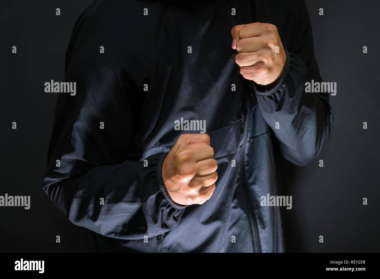 La violenza e la criminalità sulle strade, digital glitch effetto, vittima è punzonato e aggredito da aggressivo uomo violento in giacca con cappuccio, protezione CCTV camer Immagini Stock