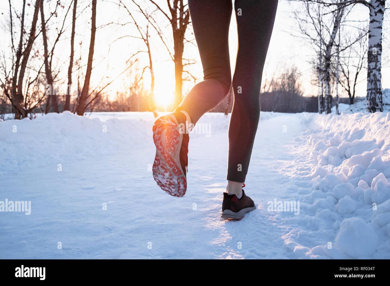 Il jogging all'aperto in inverno concetto. Le gambe di una persona di sesso femminile che corre lungo la strada innevata sulla bella giornata fredda, sparato contro il sole con lens flare Foto Stock