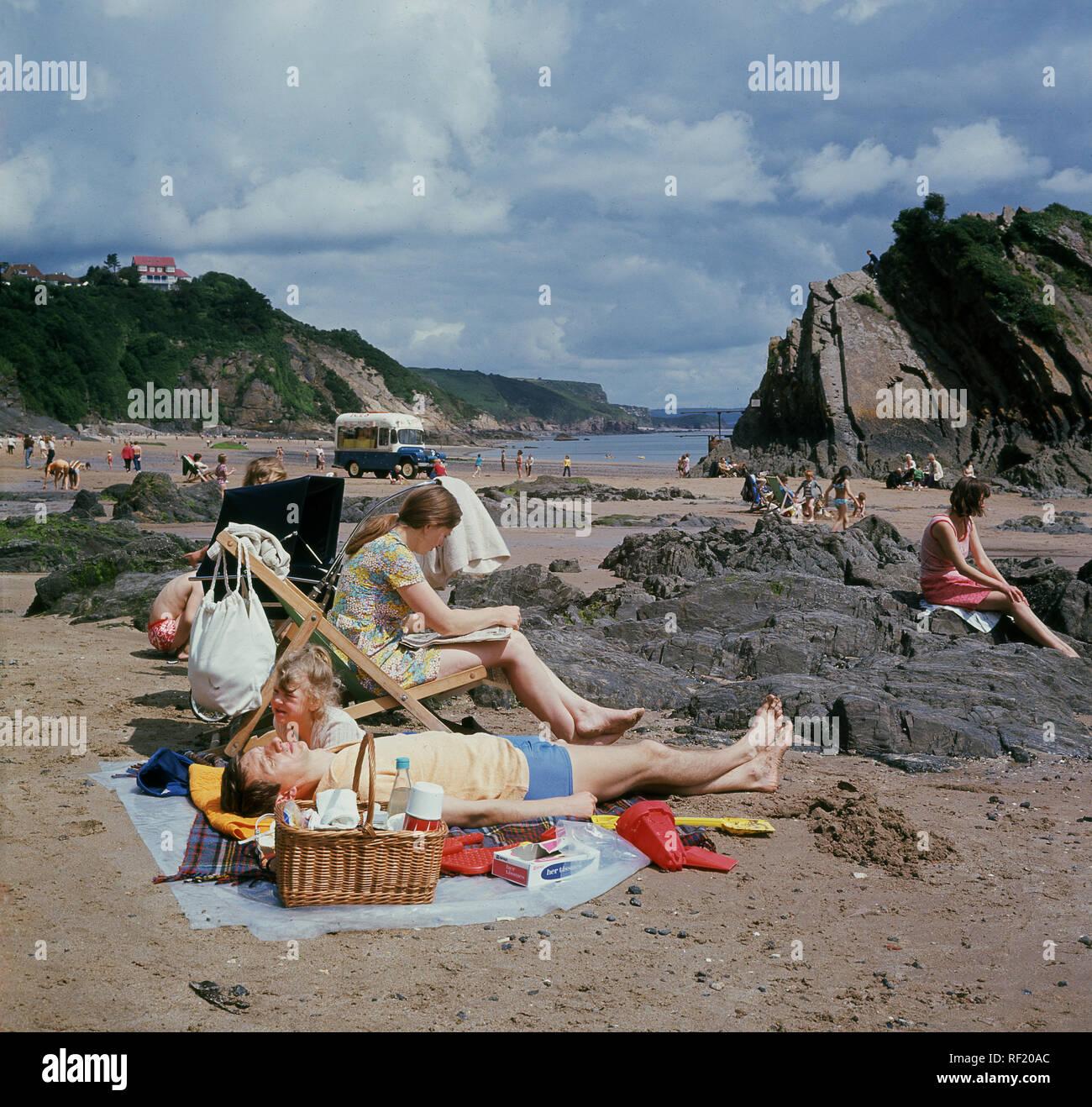 Anni sessanta, storico britannico tradizionale vacanza in famiglia...un giorno sulla spiaggia..una famiglia relax su Tenby Beach, Wales, Regno Unito. L'uomo giace su un tappeto accanto al cestino pranzo, mentre sua moglie si siede in una sedia a sdraio di lettura. Immagini Stock