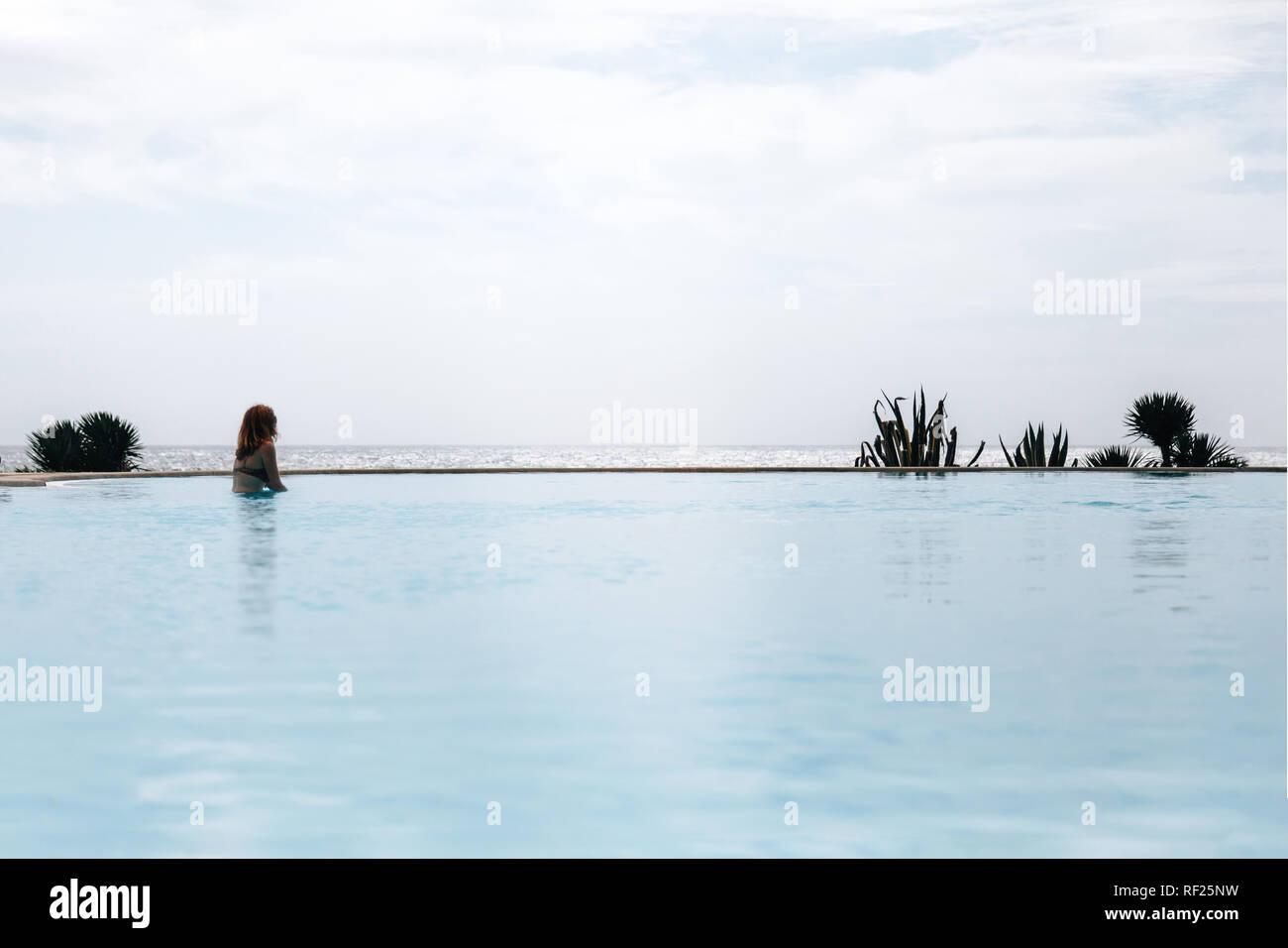 Giovane donna redhead nuoto in una piscina infinity in bikini in prossimità dell'oceano guardando lontano Foto Stock
