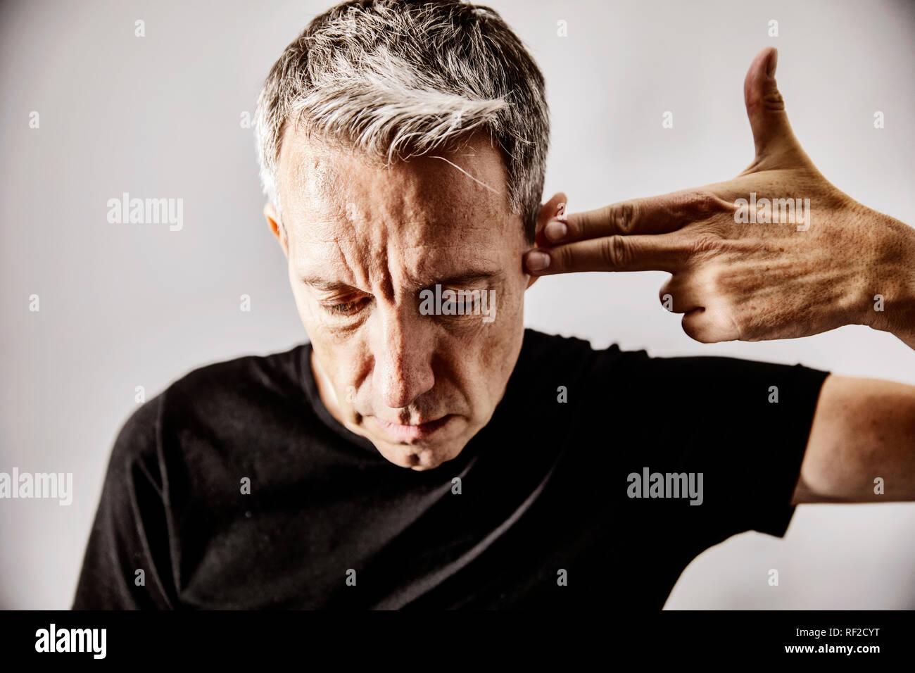 Ritratto di uomo maturo rendendo il gesto di tiro con la sua mano contro il suo tempio Immagini Stock