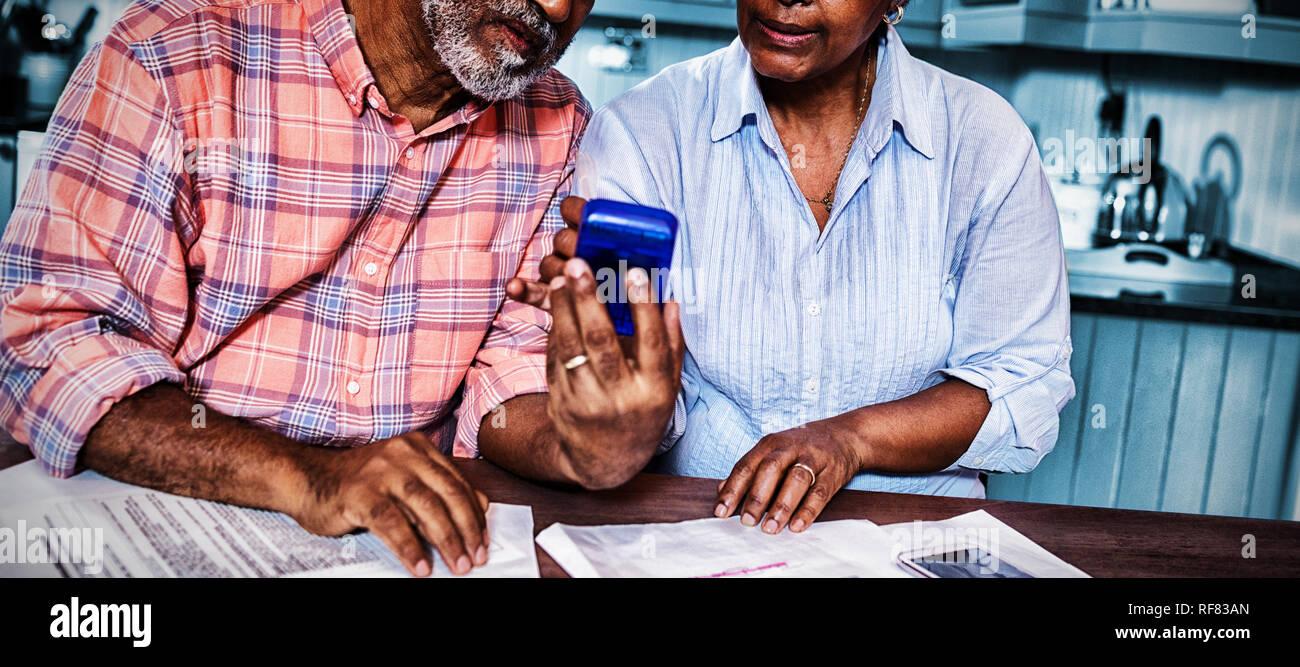 Coppia utilizzando la calcolatrice mentre discutete su documento Foto Stock