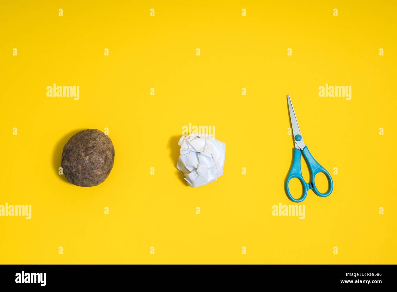 Rock, Paper, Scissors concetto. Scelta, il processo decisionale. Superiore Vista su sfondo giallo Immagini Stock
