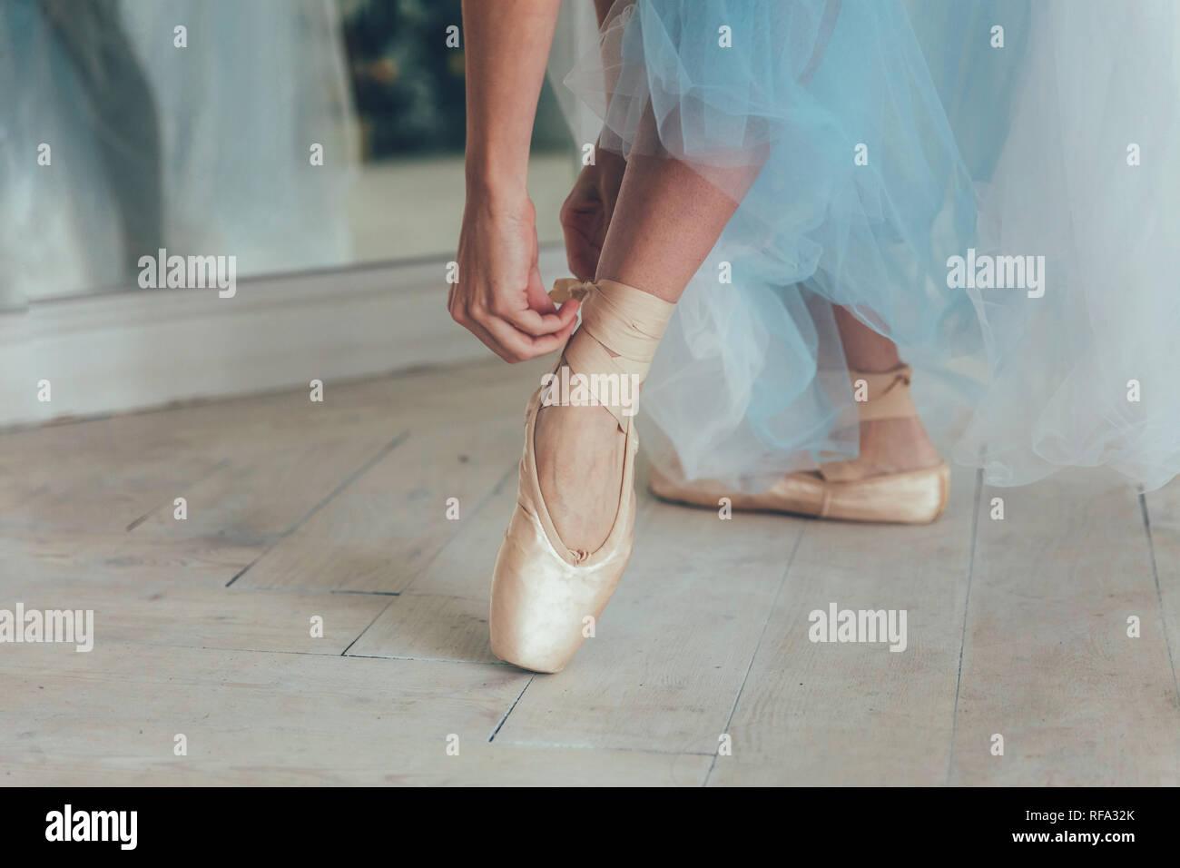 Le mani della ballerina in blu gonna tutu mette sulla pointe