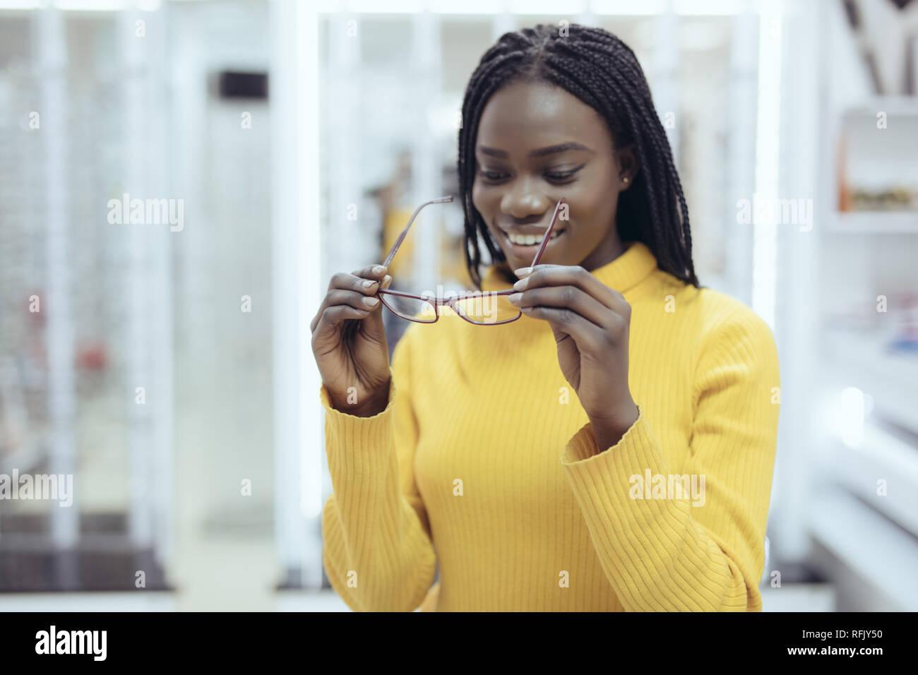 Giovane africano donna graziosa scelta di montature per occhiali in archivio  ottico. Ragazza carina di decidere per bicchieri di diverse forme e colori 29604693b52