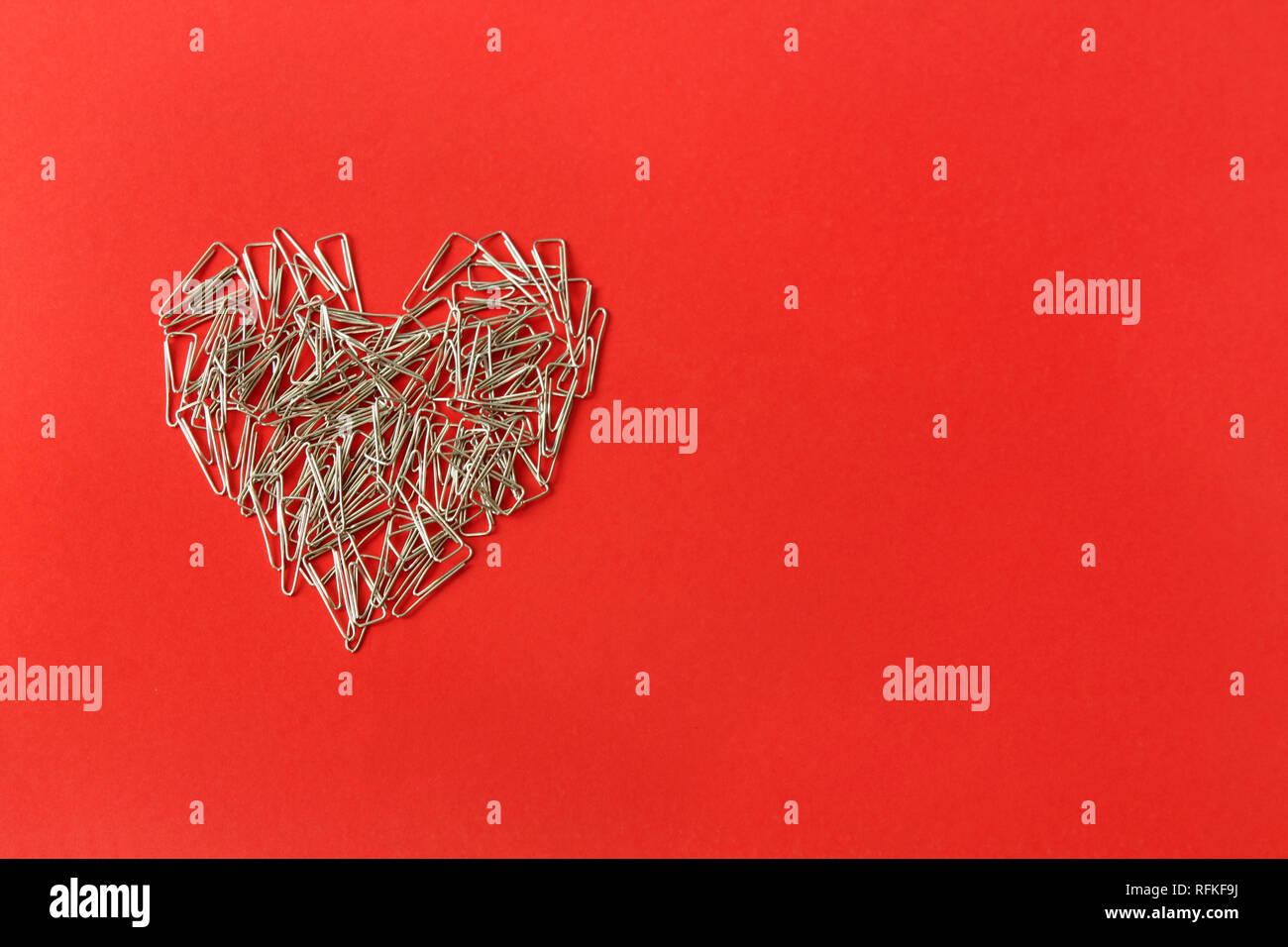 Cuore su uno sfondo di colore rosso. Il giorno di San Valentino. Il giorno di San Valentino biglietto di auguri. Cuore di clip di carta. Articoli di cancelleria. Foto Stock