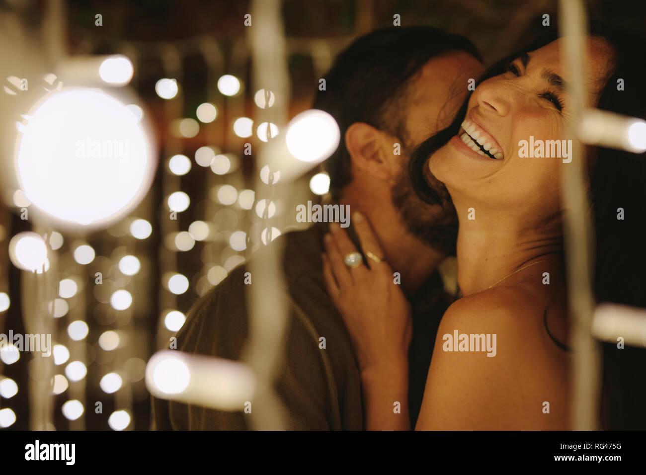 Felice coppia giovane abbracciando con luci intorno a parte. Giovane uomo e donna abbracciando e ridere. Foto Stock