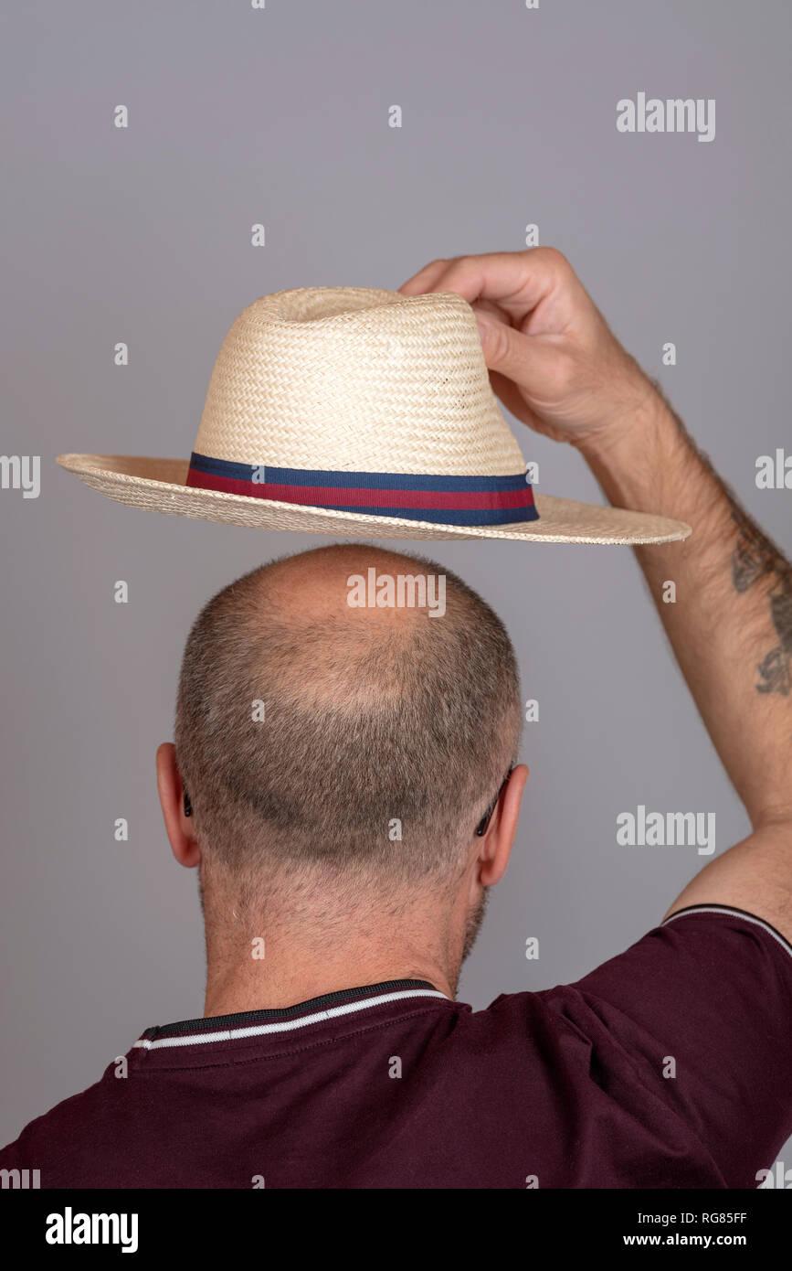 Balding uomo a mettere su un cappello di paglia per la protezione solare. Immagini Stock