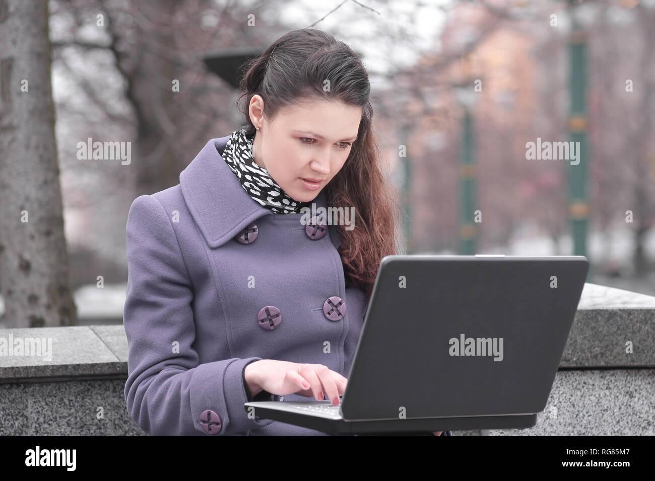 Giovane donna utilizza laptop seduto sulla panchina nel parco della città Immagini Stock