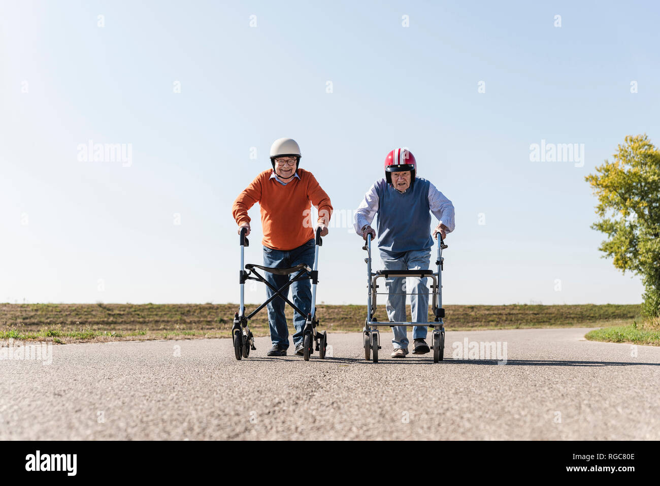 Due vecchi amici che indossa caschi di sicurezza, gareggiando in una carrellata di gara dello scuotipaglia Immagini Stock