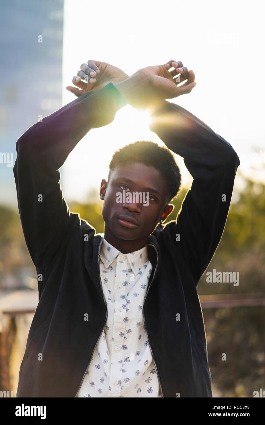 Giovane uomo bracci di sollevamento con polsi incrociati Foto Stock