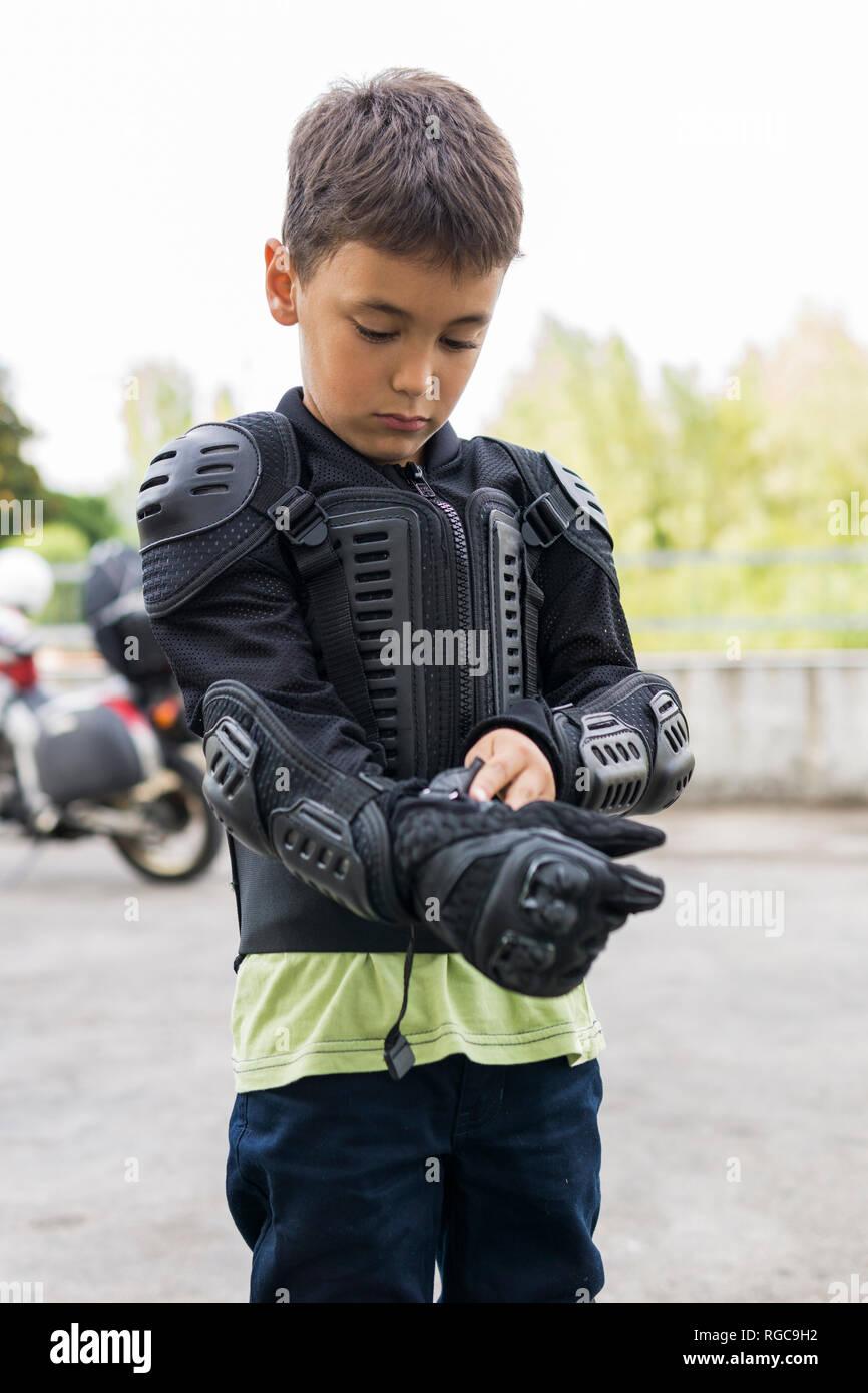 Ragazzo mettendo su abbigliamento protettivo per la preparazione di un viaggio in moto Immagini Stock