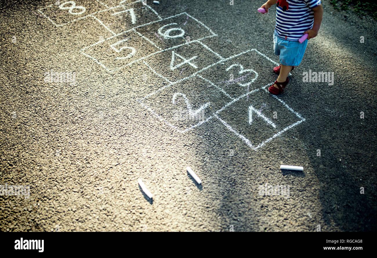 Bambina con tratte campana sulla strada, vista parziale Immagini Stock