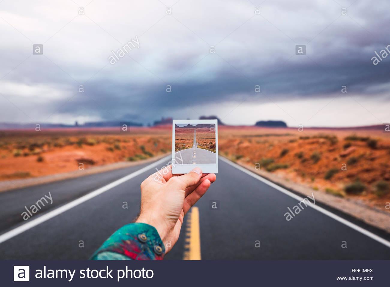 Stati Uniti d'America, Utah, mano azienda instanf foto su strada alla Monument Valley Immagini Stock