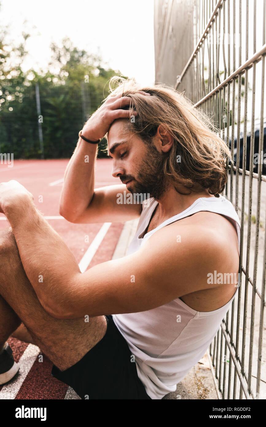 Giovane uomo seduto sul basket, stanchi e delusi Immagini Stock
