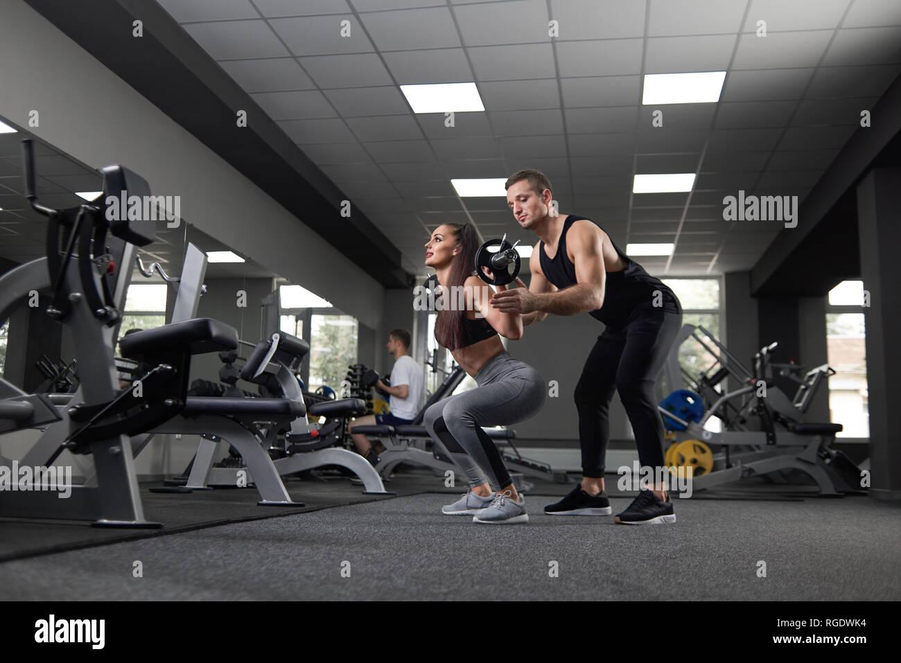 Montare la donna facendo squat e sollevamento barbell