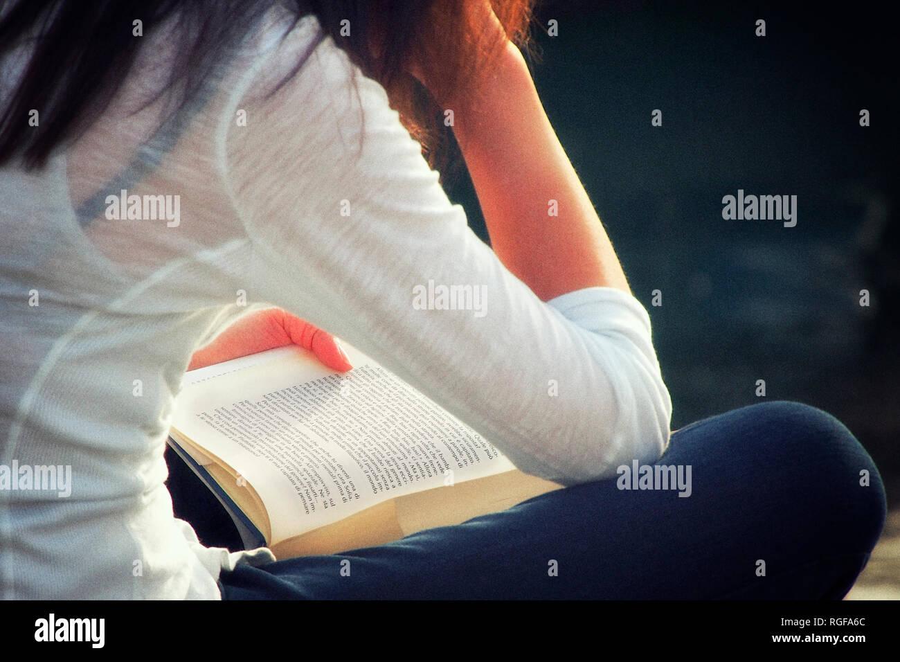 Una ragazza sta leggendo un libro in aria aperta e seduto. Immagini Stock