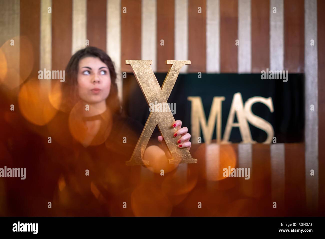 Giovane donna tenendo la lettera x della parola xmas rivestito in oro cercando nella credenza. Immagini Stock